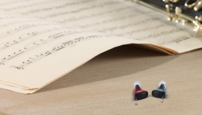 Audio Service: Zwei Im-Ohr-Hörgeräte auf einem Tische neben Noten