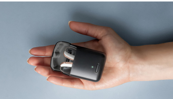 Audio Service: Eine Hand hält einen offenen Charger mit zwei AudioService Stiline G6 Hörgeräten