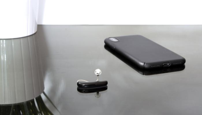Audio Service: Ein schwarzes Hörgerät neben einem Smartphone auf einem Tisch