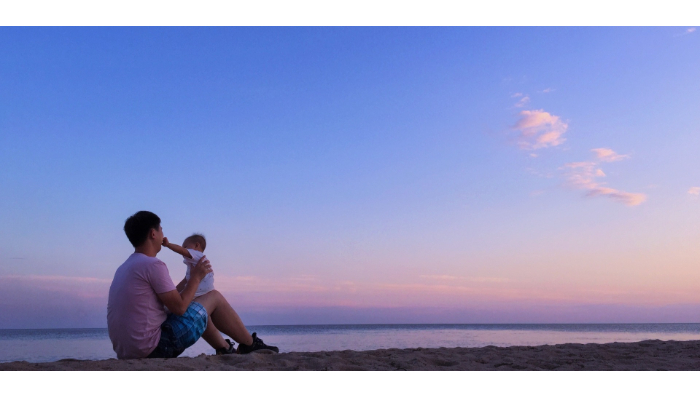 Bernafon: Vater mit Baby am Strand