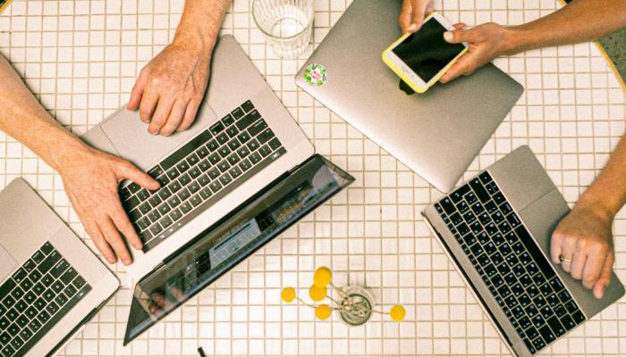 Bernafon: arbeitende Menschen am Tisch von oben mit Laptop