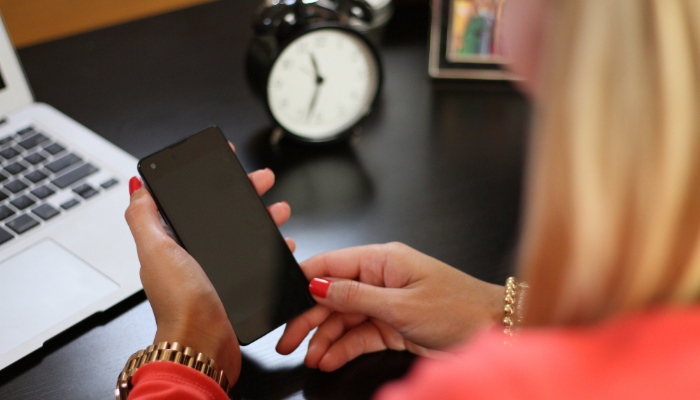 Bernafon: Frau hält ein Handy in der Hand