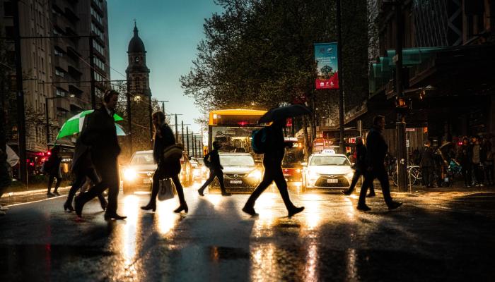 Bernafon: Menschen laufen bei Regen durch die Stadt