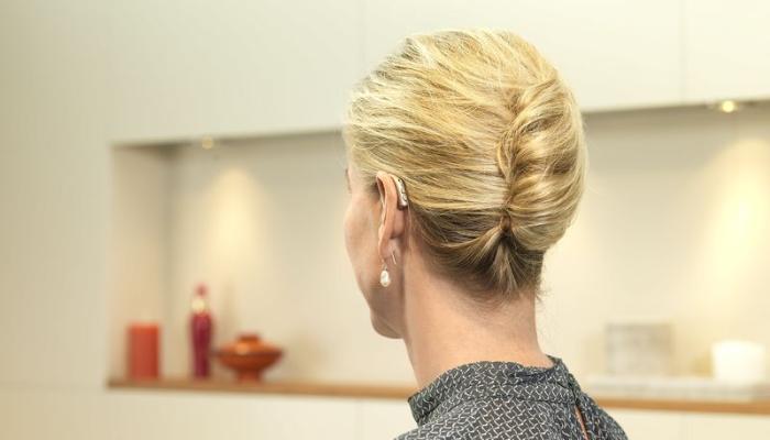Bernafon: Frau von hinten mit Högerät am Ohr