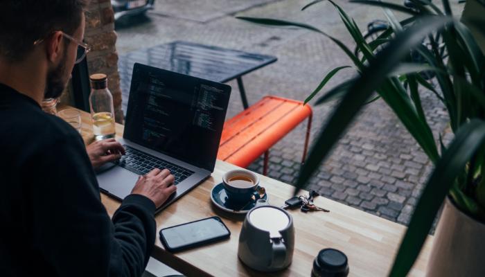 Bernafon: Mann sitzt vor seinem Laptop im Cafe