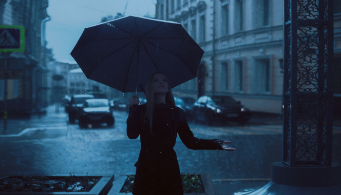 Hansaton: Frau im Regen unterm Regenschirm