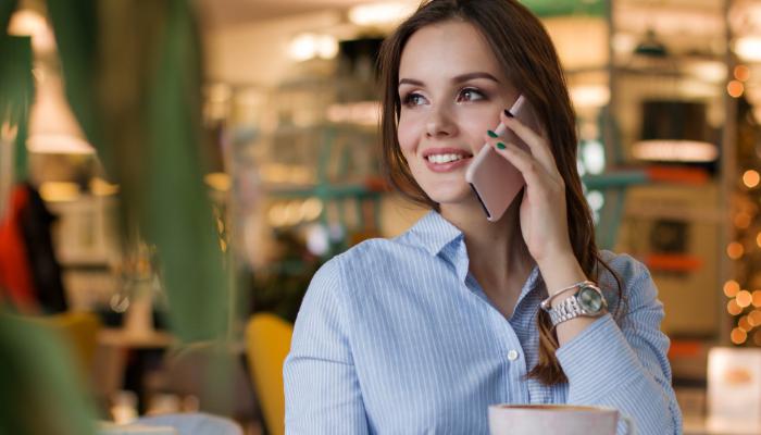 Hansaton: Frau sitzt im Café und hat Smartphone am Ohr