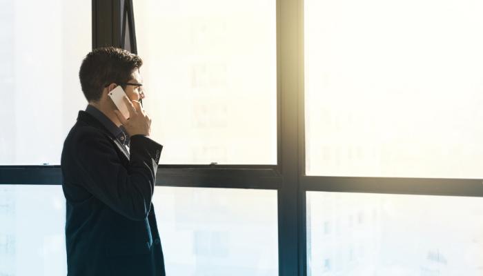 Hansaton: Mann steht am Fenster und hat Smartphone am Ohr