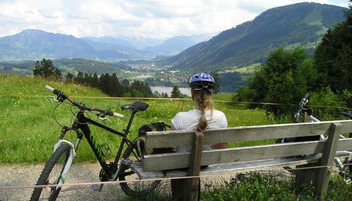 Hansaton: Frau sitzt auf einer Bank und schaut in die Landschaft, ihr Fahrrad steht daneben.