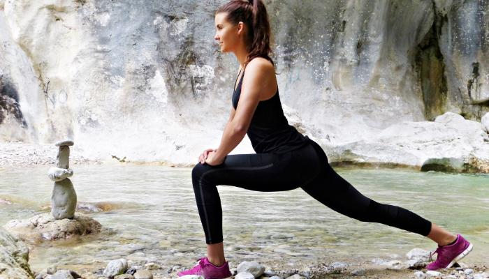 Hansaton: Frau macht Yoga am Meer vor einem Felsen