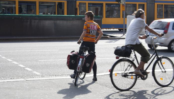 Hansaton: Zwei Radfahrer an belebter Straße in einer Stadt