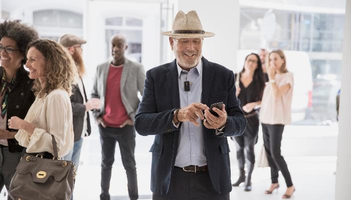 Oticon: Mann mit Hut tippt auf seinem Smartphone