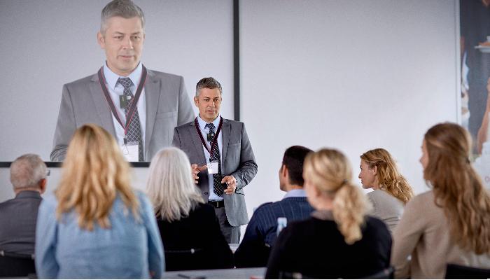 Oticon: Vortragsraum mit Redner vor einer Leinwand