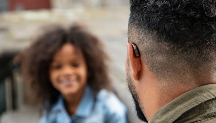 Oticon: Mann spricht mit Kind