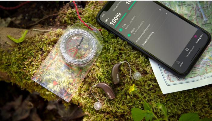 Oticon: Hörgeräte auf Waldboden mit Handyapp
