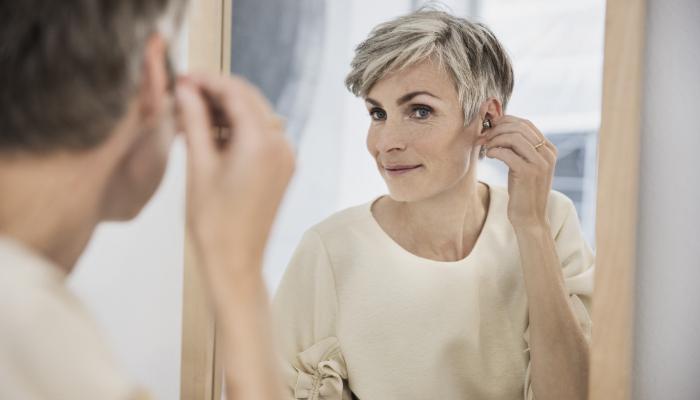 Oticon: Frau setzt Im-Ohr-Gerät ins Ohr