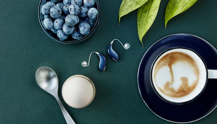 Oticon: Oticon-Hörgeräte neben Blaubeeren und Kaffee auf einem Tisch