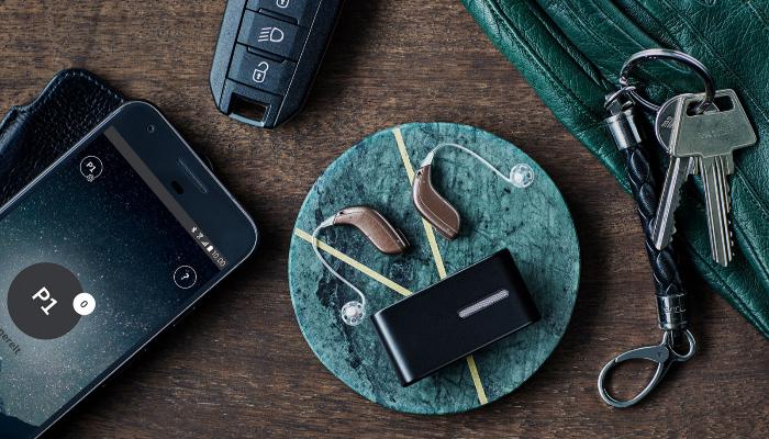 Oticon: Oticon-Hörgeräte liegen auf Tisch mit Mikro, Handy und Schlüssel