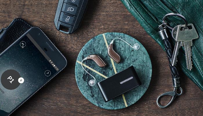 Oticon: Hörgeräte liegen auf Tisch mit Mikro,Handy,Schüssel