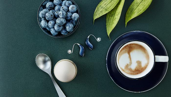 Oticon: Hörgeräte neben Blaubeeren und Kaffee auf einem Tisch