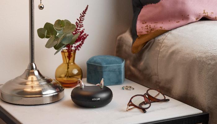 Oticon: Ladegerät mit Hörgeräten und Brille auf Nachttisch
