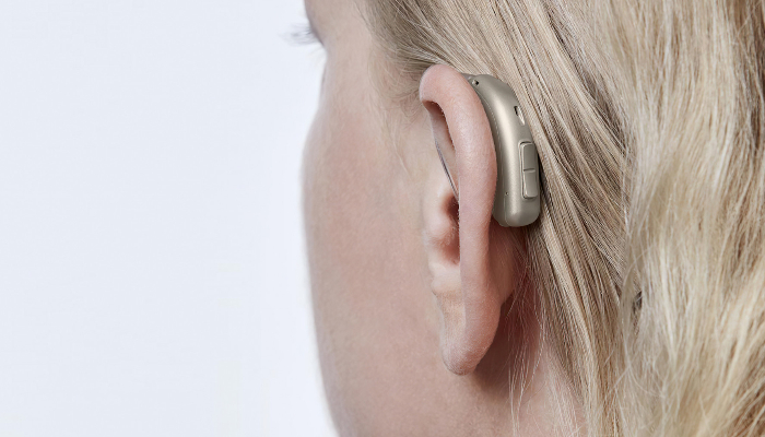 Oticon: Ein Oticon-Hörgerät am Ohr einer Frau