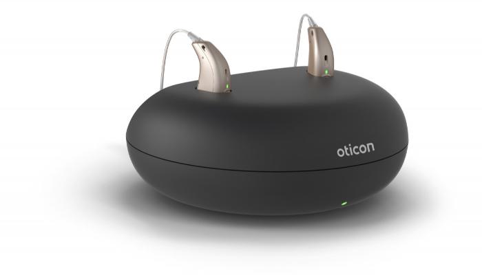 Oticon: Zwei Oticon-Hörgeräte stecken in einer Akku-Ladestation