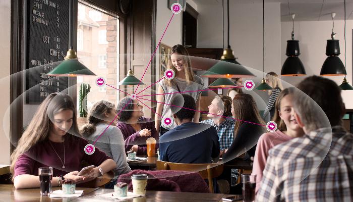 Oticon: Teenager in einem gut besuchten Café