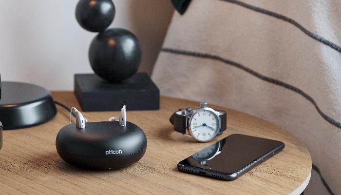 Oticon: Akku-Ladegerät mit 2 Hörgeräten und Handy auf Nachtisch