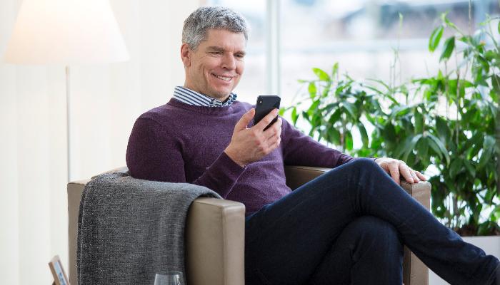 Oticon: Mann auf Sofa mit Smartphone