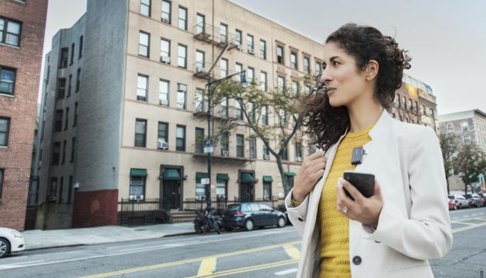 Oticon: Frau mit Handy und Ansteckmikrofon