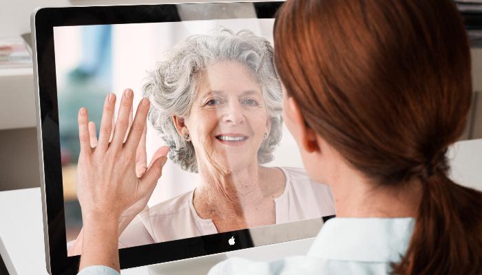Oticon: Frau mit Blick aufs Laptop beim Skypen