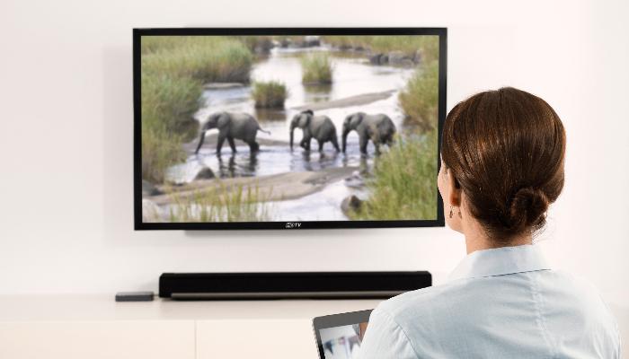 Oticon: Frau beim Fernsehen mit Hilfe eines TV-Adapters