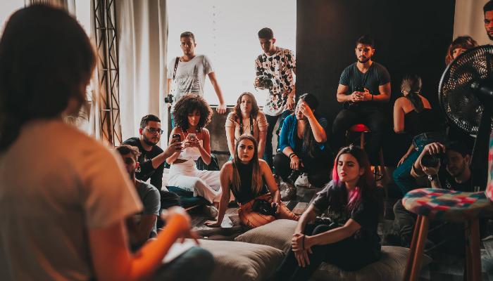 Audio Service: Viele junge Menschen hören einer Person im Raum zu