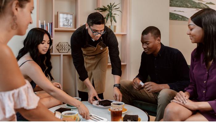 Audio Service: Fünf Menschen um einen kleinen Tisch mit Gebäck und Kaffee