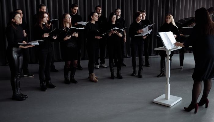 Audio Service: Schwarz gekleideter Chor und weißes Dirigentenpult