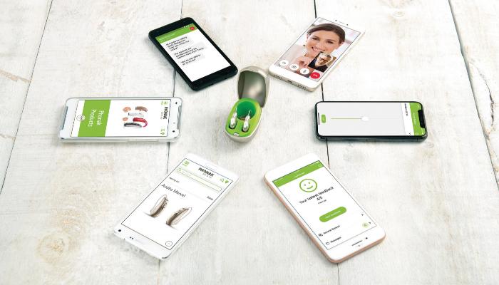 Phonak: Zwei Phonak-Hörgeräte in einem Etui, drumherum liegen Smartphones
