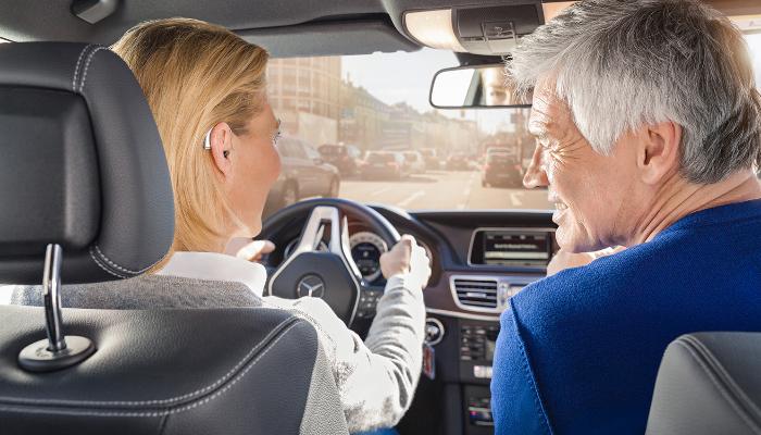 Phonak: Mann und Frau im Auto, Frau fährt, sie trägt ein Hörgerät