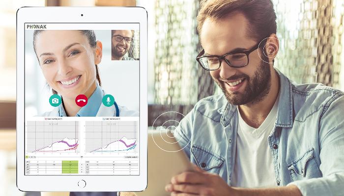 Phonak: Ein Mann mit Brille schaut auf ein Tablet und lacht