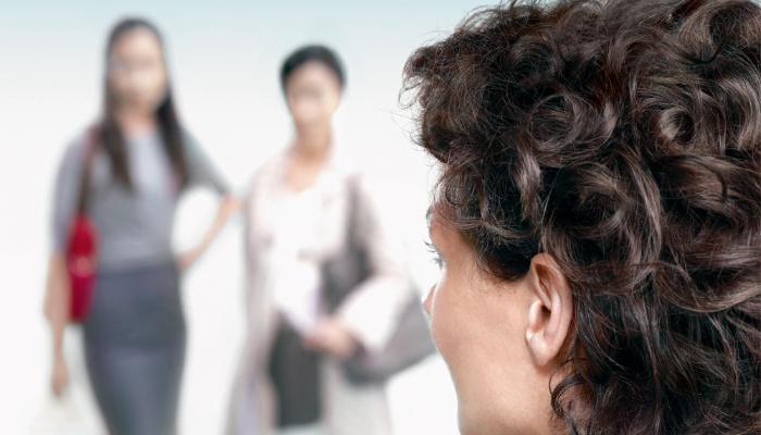 Phonak: Frau hört zwei Frauen zu, die vor Ihr stehen