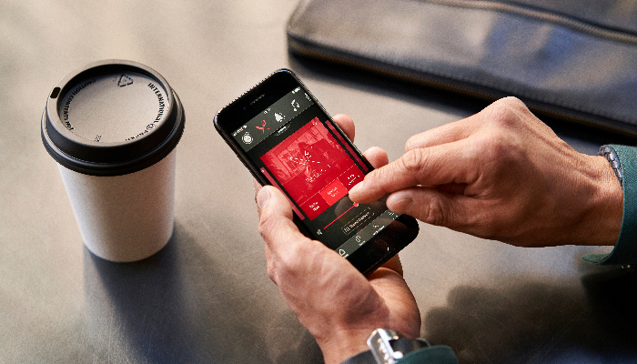 ReSound: Smartphone in der Hand, die andere Hand tippt in der App, daneben Kaffeebecher