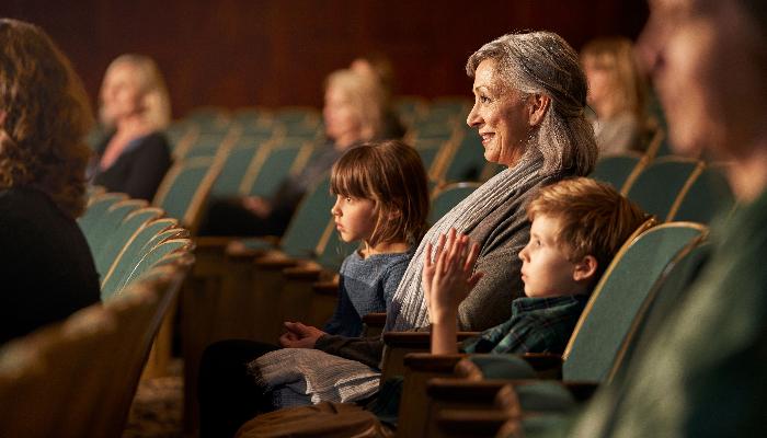 ReSound: Familie sitzt im Auditorium und schaut zur Bühne