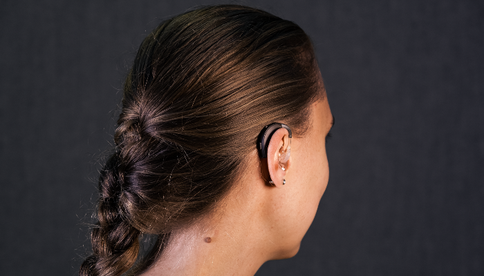 ReSound: Frau von hinten, Hörgerät mit Winkel am Ohr
