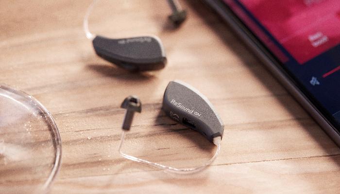 ReSound: Hörgeräte liegen auf einem Tisch neben einem Handy