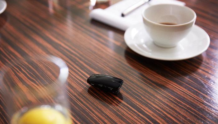 ReSound: Mikrofon auf dem Tisch liegend, mit Wasserglas und Kaffeetasse