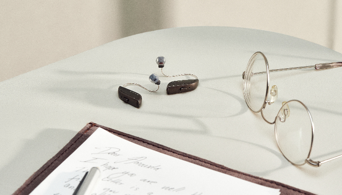 ReSound: Zwei Hörgeräte neben Brille und Schreibblock