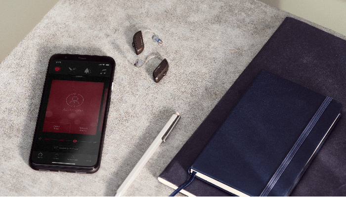 ReSound: Zwei Hörgeräte neben Smartphone und Notizbuch