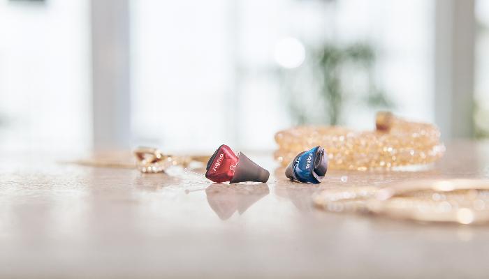 Signia: Ein Paar Standard-Im-Ohr-Hörgeräte mit Dome auf dem Tisch neben Schmuck
