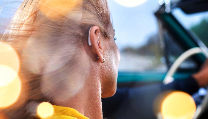 Signia: Frau sitzt im Auto und hat ein Styletto am Ohr