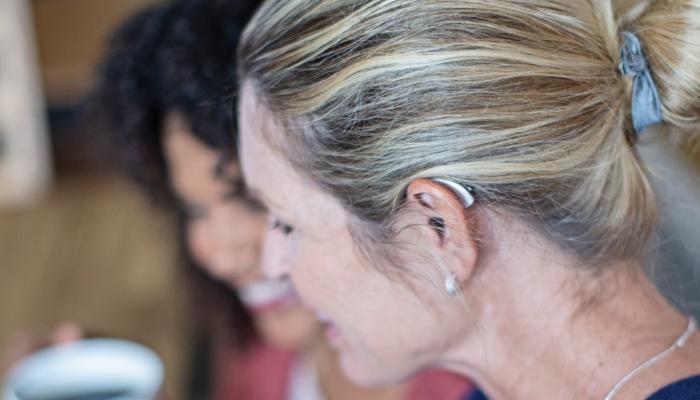 Starkey: Frau mit Hinter-Dem-Ohr-Hörgerät